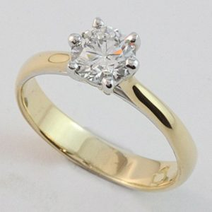 Six claw solitaire with the claws oriented across the finger on a 'soft' hammered band in 18 carat yellow and white gold.