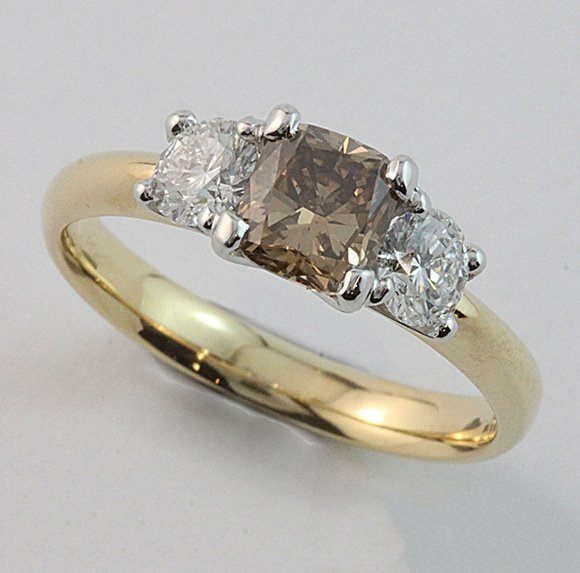 A claw-set three stone ring with an cushion-cut Australian Argyle champagne diamond centre flanked by brilliant-cut white diamonds.