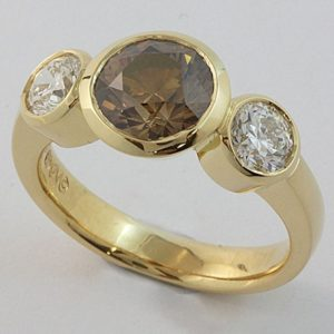 A rubbed-in set three stone ring featuring an Australian Argyle cognac diamond in the centre.
