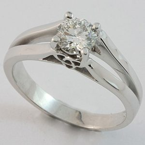 Solitaire diamond ring with split band and three-point Celtic knot detail under setting.