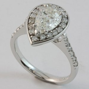 18 carat white gold pear shaped halo engagement ring with diamond set shoulders.
